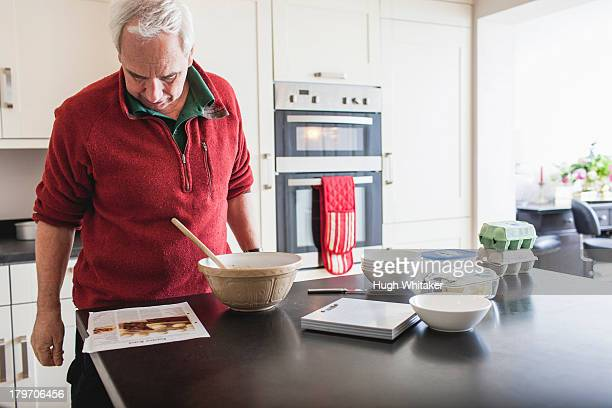 Senior male studying recipe on kitchen counter