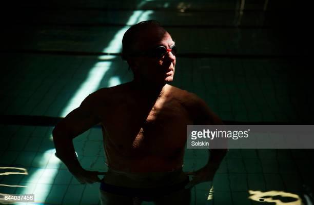 senior male swimmer standing in swimming pool