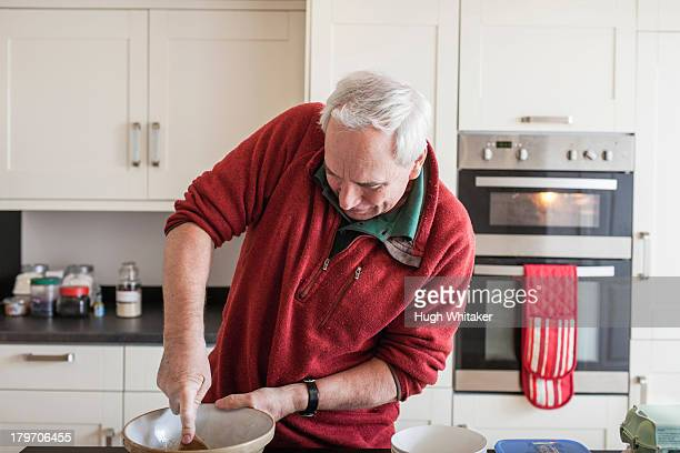 Senior male using wooden spoon in mixing bowl