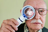 Senior man holding an illuminated magnifying glass he uses to help him read because he suffers from Wet Macular Degeneration.