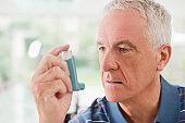 Senior man about to use asthma inhaler