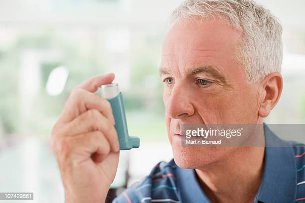 Senior man about to use asthma inhaler