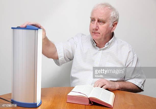 senior man adjusts seasonal affective disorder SAD lamp