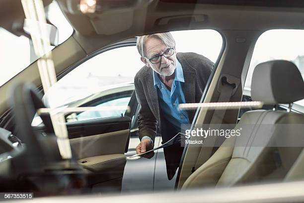 Senior man admiring car displayed in store