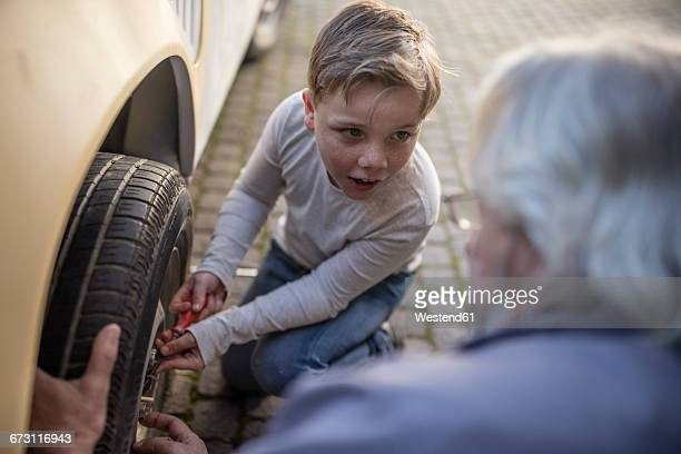 Senior man and boy changing car tire