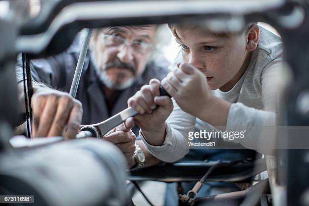 Senior man and boy working on mechanism of a car