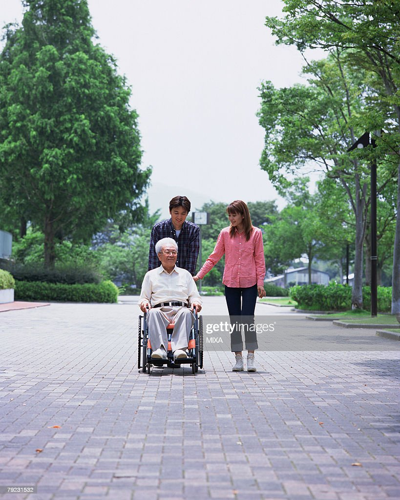 A senior man and children walking in a park : Stock Photo