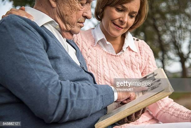 Senior man and daughter looking at photo album