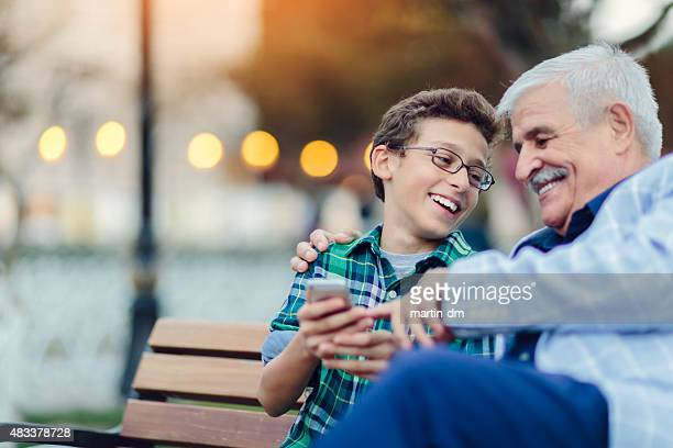 Senior man and early teen boy using smartphone together