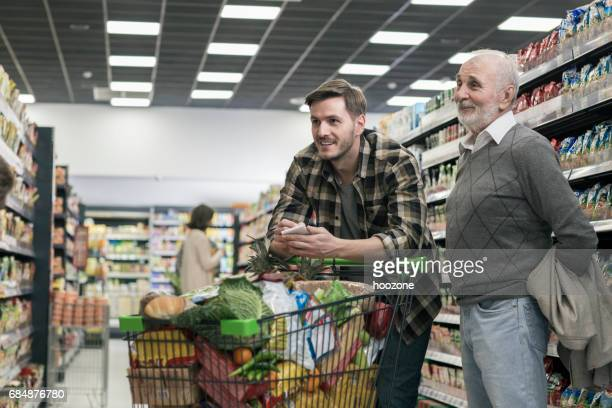 Senior man and his son shopping in supermarket