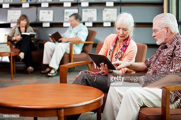 Idoso e a sua esposa a ler notícias sobre tablet digital