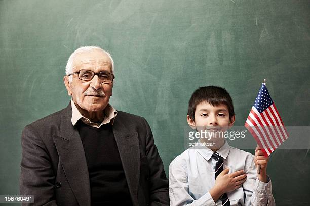 Senior man and little boy posing with American Flag