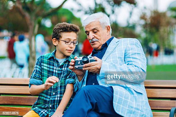 Senior man and little boy with retro camera