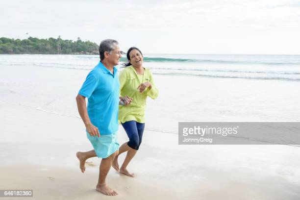 Senior man and mature woman laughing and jogging on beach