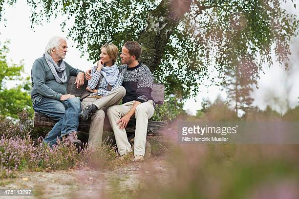 Senior man and mid adult couple sitting on log