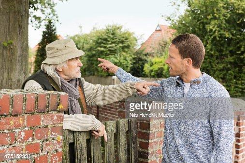 Senior man and mid adult man arguing