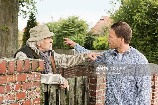 Senior man and mid adult man arguing