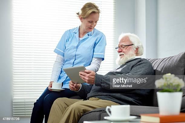 Senior homme et infirmière à l'aide de tablette numérique à la maison
