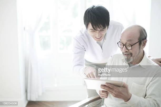 Senior man and son using digital tablet