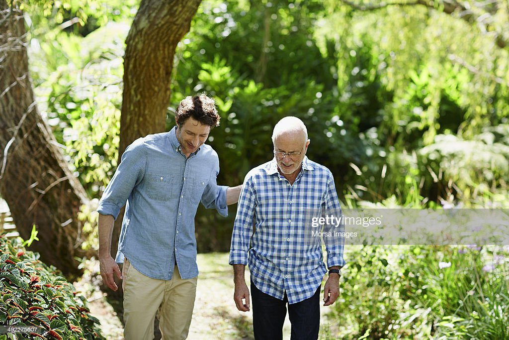 Senior man and son walking in park : Stock Photo
