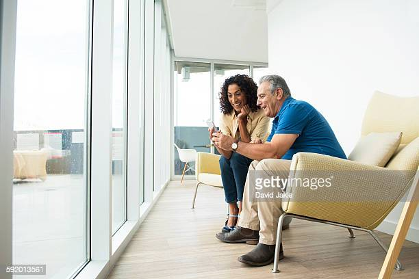 Senior man and wife reading smartphone texts