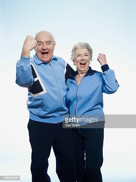 Senior man and woman in sportswear cheering