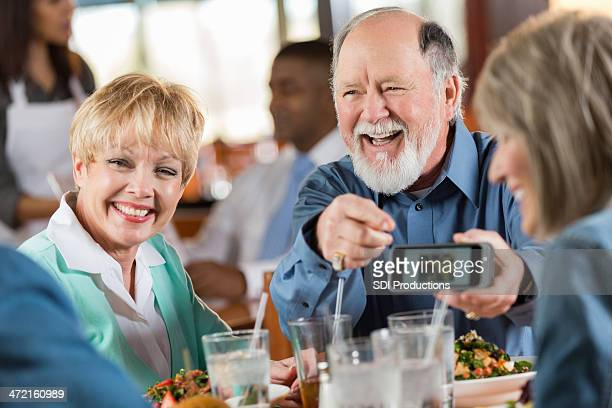 Senior man and woman laugh with friends over meal