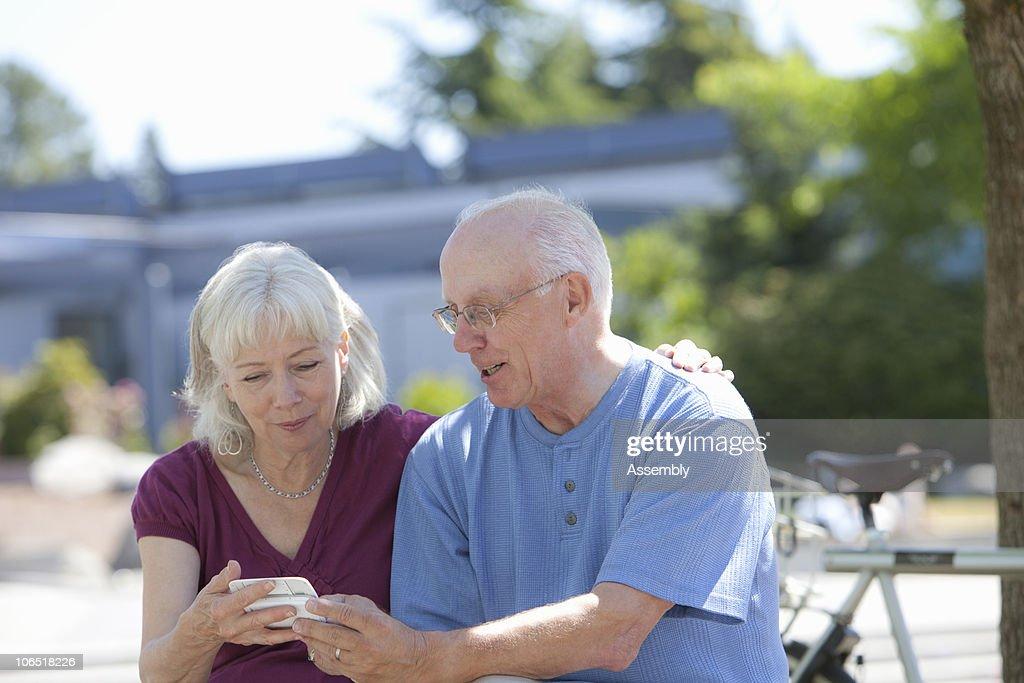 senior man and woman looking at phone outside : Stock Photo