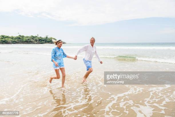 Senior man and woman running in sea holding hands