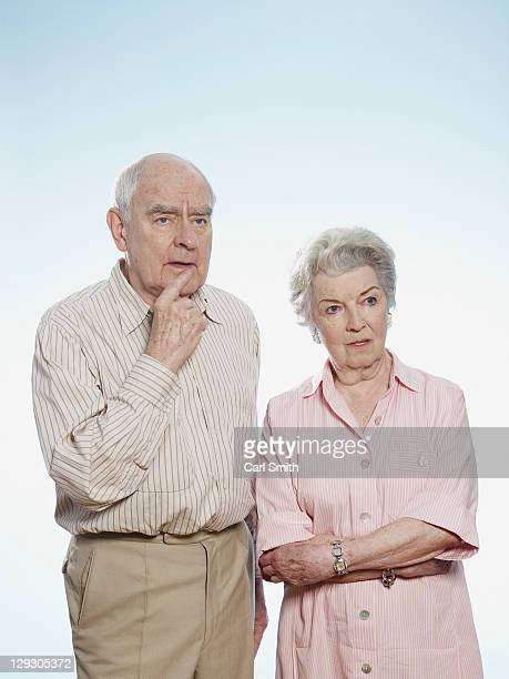 Senior man and woman side by side pondering