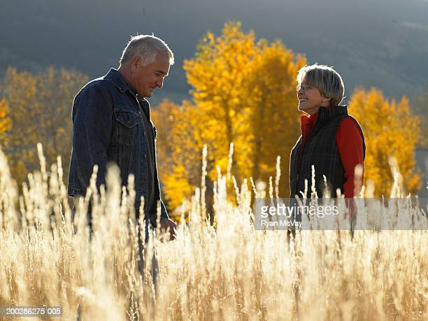 Senior man and woman standing in field of tall grass, side view