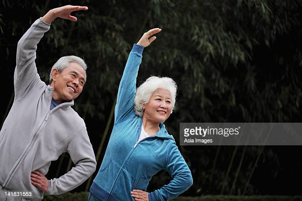 Senior man and woman stretching together