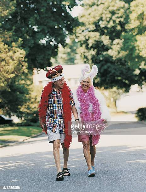 Senior Man and Woman Walking Down a Surburban Road Wearing a King and a Rabbit Costume