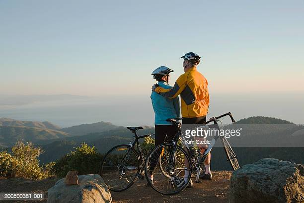 Senior man and woman with bicycles on hillside, sunset, rear view