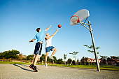 Senior man and young man playing basketball on outdoor court
