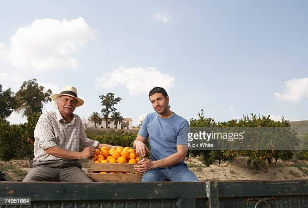 Senior man and young man sitting by crate of oranges, portrait