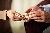 Senior man and young woman holding old pocket watch, close-up of hands