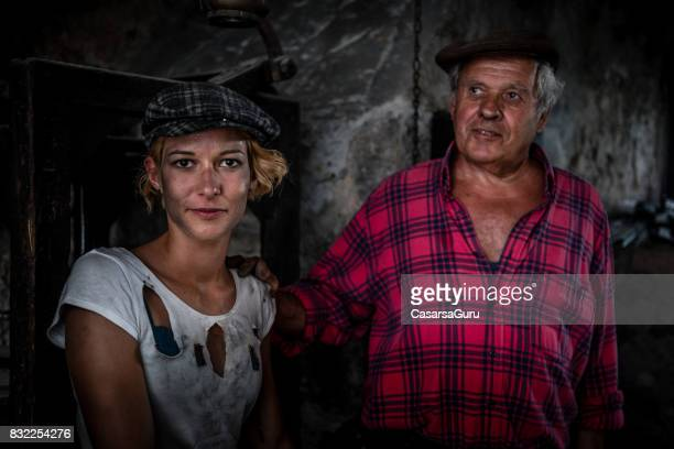 Senior Man and Young Woman in Blacksmith Shop