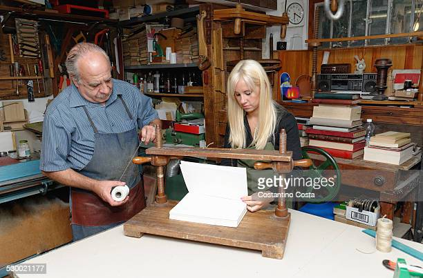 Senior man and young woman preparing to bind pages with thread in traditional bookbinding workshop