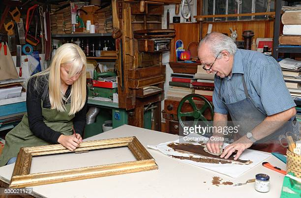 Senior man and young woman restoring picture frame and book spine in traditional bookbinding workshop