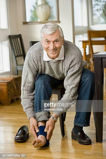 Senior man applying ankle brace, smiling, portrait