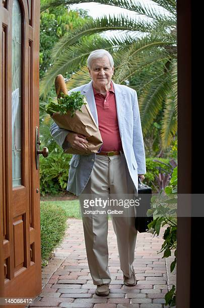 A senior man arriving home with a bag of groceries and a briefcase