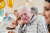 Happy senior man at a birthday party with his friends and family. He is sitting at the table smiling for the camera with his head resting on his hand.