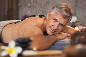 Portrait of senior man with hot stones on massage table looking at camera. Smiling mature man pampering himself at spa with body treatment. Man with grey hair lying naked and relaxing during hot stone