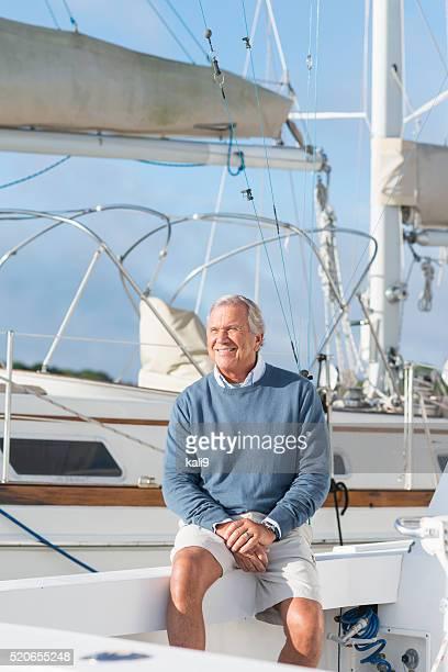 Alter Mann im Boot-dock sitzt auf Jacht