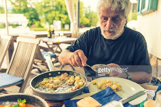 Senior man at dinner on terrace