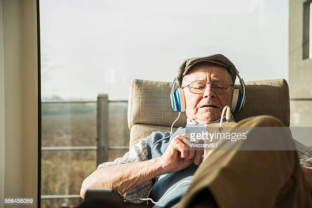 Senior man at home relaxing with headphones
