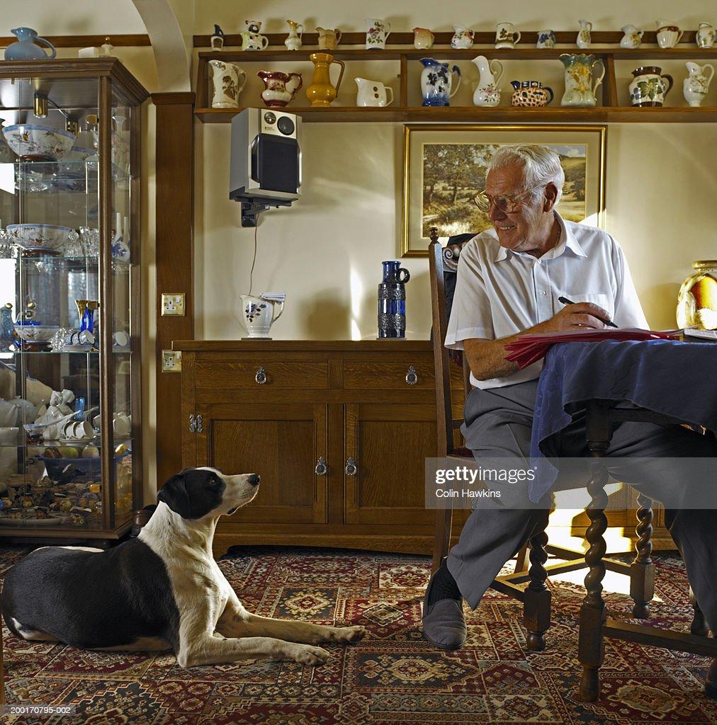 Senior man at table looking down at dog, smiling : Stock Photo