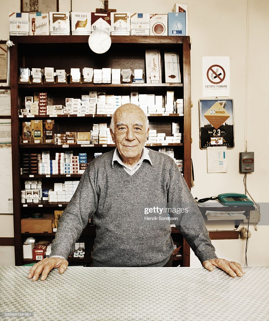 Senior man behind counter in tobacconists, portrait