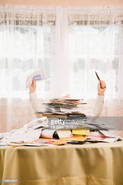 Senior man behind pile of bills